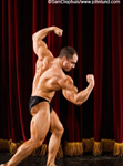 Picture of a bodybuilder posing for the audience and judges in a body building contest. The man is bend slightly at the waist and flexing his various muscle groups.